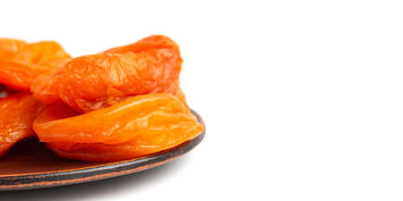 Dried apricots fruit in a plate, isolated on white background, close up view. 免版税图像