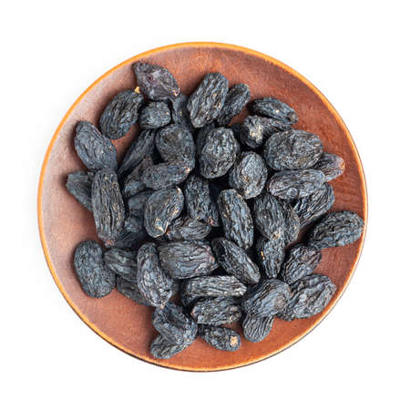 Dark blue raisins on a plate isolated on white background, top view.