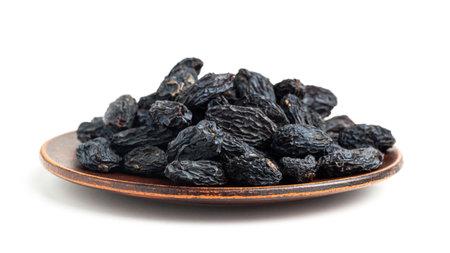 Dark blue raisins on a plate isolated on white background. 免版税图像