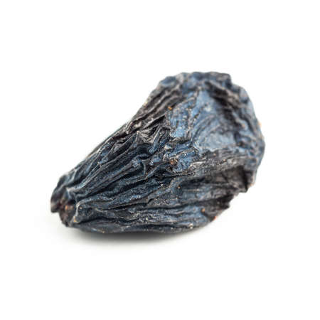 Dark blue raisins isolated on white background, close-up view.