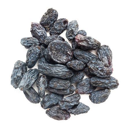 Dark blue raisins isolated on white background, top view. 免版税图像