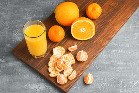 Glass of fresh orange juice, whole and sliced fruits on wooden board on gray background with copy-space.
