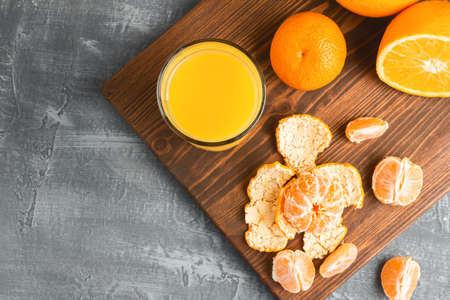 Glass of fresh orange juice, whole and sliced fruits on wooden board, top view with copy-space. 免版税图像