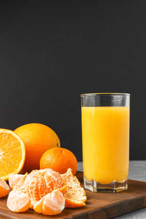 Glass of fresh orange juice, whole and sliced fruits on wooden board on dark background with copy-space.