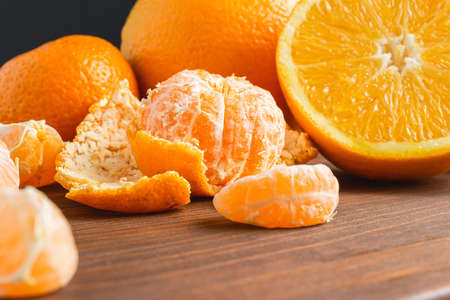 Tangerine, mandarin pieces and orange fruit, whole and sliced citruses on wooden board.