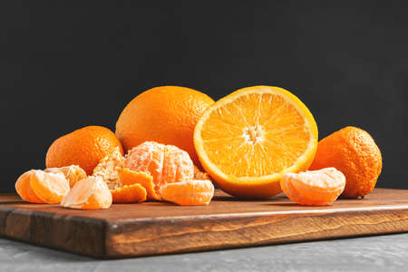 Tangerine, mandarin pieces and orange fruit, whole and sliced citruses on wooden board on dark background with copy-space.