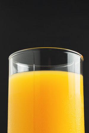 Glass of fresh orange juice on dark background. 免版税图像