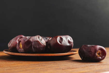 Dried organic date fruits in a plate on wooden table with dark background.