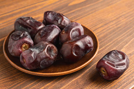 Dried organic date fruits in a plate on wooden table.