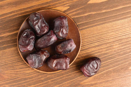 Dried organic date fruits in a plate on wooden table, top view.