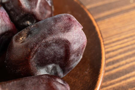 Dried organic date fruits in a plate on wooden table, close-up view.