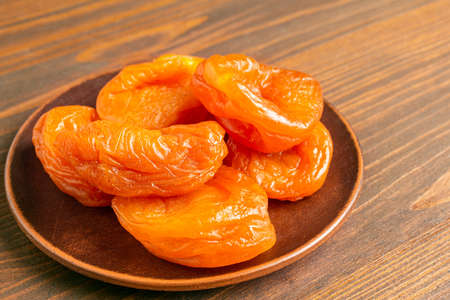 Dried apricots fruit in a plate on wooden table, close up view.