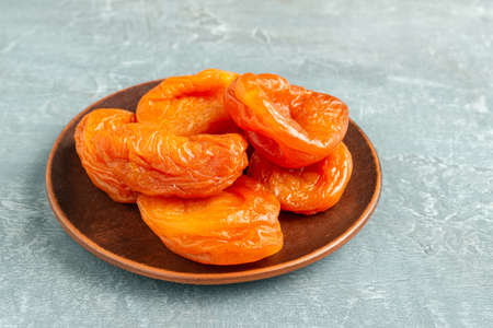 Dried apricots fruit in a plate on gray background, close up view.