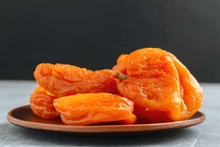 Dried apricots fruit in a plate on dark background with copy space. 免版税图像