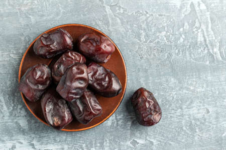 Dried organic date fruits in a plate on a gray background top view.