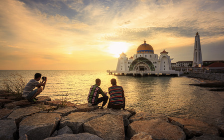 tourist attraction: Three traveler with beautiful sunset  - at Malacca Straits Mosque ( Masjid Selat Melaka). It is a mosque located on the man-made Malacca Island near Malacca Town, Malaysia. Stock Photo