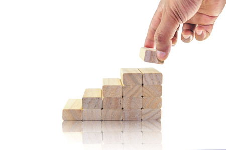 wood block: Hand aranging wood block stacking as step stair. Business concept for growth success process. Stock Photo