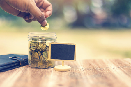 Saving money concept. Hand putting money coin stack growing business