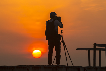 silhouette of photographer taking picture of landscape during sunrise Stock Photo
