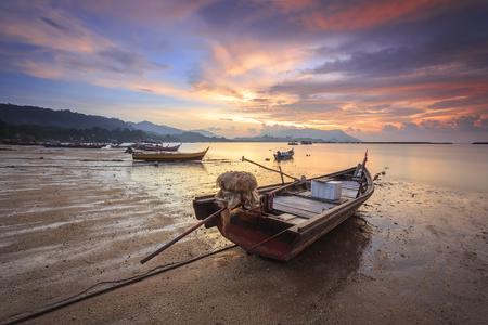 Paisaje hermoso de la puesta del sol del pueblo del pescador en el pueblo negro de la playa de la arena en Langkawi, Malasia. Foto de archivo