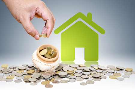 Male hand putting money coins with green home, Saving for buy home concept