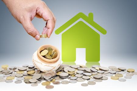 Mâle main mettant des pièces d'argent avec la maison verte, économiser pour acheter le concept de maison