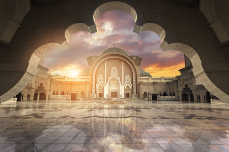 In framming Muslim pray at the mosque with harsh sunset light and high contrast in amazing beautiful dramatic sky Stock Photo