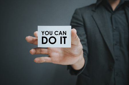 Man holding white card with quotes U CAN DO IT on wall background