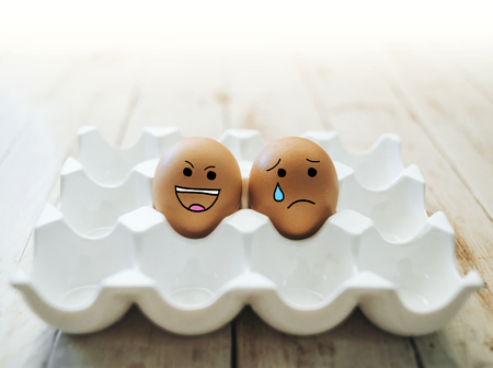 Set of eggs emotion on wood background. Happy and unhappy smileys. Stock Photo