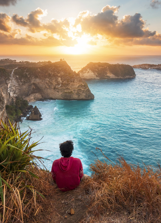 Enjoying life. Young man looking at the sea with sunrise view. Vacations lifestyle concept. Bali, Nusa Penida, Indonesia. 免版税图像