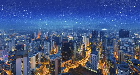 Panoramic building modern business district at night with lines and dots of connection in the sky. Wireless internet network in smart city. 版權商用圖片