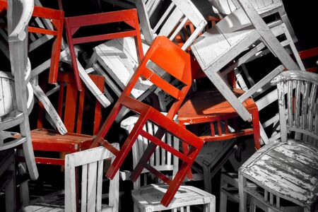 Wooden chairs. Outstanding red chair of black and white Pile of chairs. Chairs conceptual.