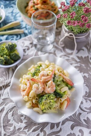 Italian pasta fettuccine in a creamy sauce with shrimp on a plate.