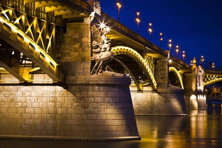 Beautifully lit Margaret bridge over the Danube at dusk in Budapest, Hungary photo