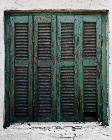Achient wooden turquoise window on a white house in Sarti, Greece photo