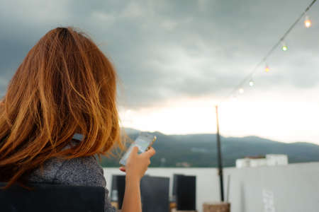 she: She look at mountain view with mobile and blur mountain view for feeling Stock Photo