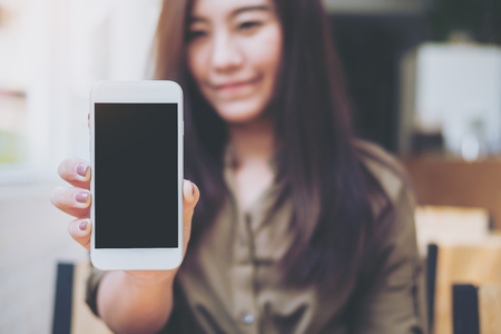 Mockup image of a beautiful woman holding and showing white mobile phone with blank black screen with smiley face in vintage wooden cafe