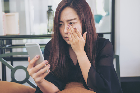 A beautiful asian woman looking at smart phone with feeling sad and cry in cafe Stock Photo