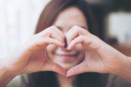 Una mujer de cara sonriente haciendo la mano del corazón firme sobre su rostro con amor
