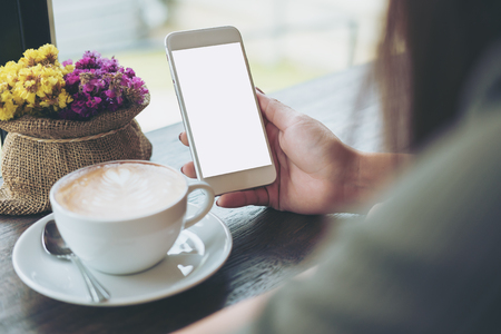 Mockup image of hands holding white mobile phone with blank white screen with hot coffee cup and flower vase in cafe Banco de Imagens - 77517870