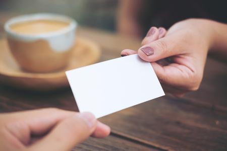 Bedrijfsmens die adreskaartje geven aan bedrijfsvrouw met koffiekop op houten lijstachtergrond