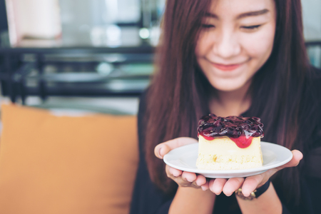 A beautiful asian woman holding  blueberry cheese cake  with feeling happy and good lifestyle in modern cafe Stock Photo