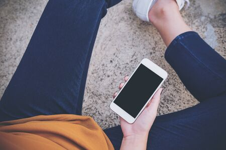 sitting on the ground: Mockup image of a woman sitting on the street and holding white mobile phone with blank black screen