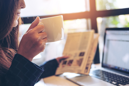 A business woman reading newspaper ,drinking coffee and using laptop in the morning in office Stock Photo