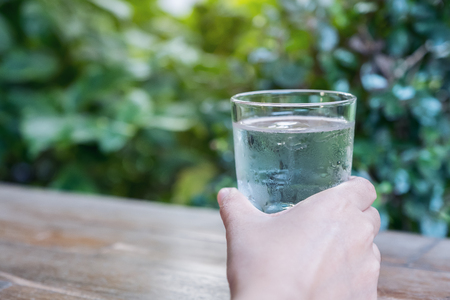 Closeup image of a hand holding a glass of cold water on wooden table with green nature background