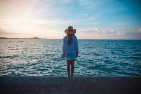 찾고 바다와 일몰 배경으로 해변에서 볼 수있는 여자 스톡 콘텐츠