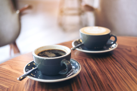 Closeup image of two blue cups of hot latte coffee and Americano coffee on vintage wooden table in cafe Stok Fotoğraf