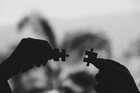 Imagem preto e branca de duas mãos segurando um quebra-cabeça com sentimento amor
