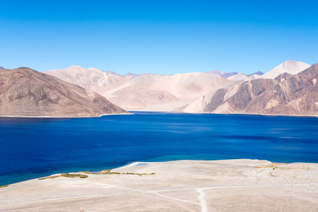 Landscape image of Pangong lake with mountains view and blue sky background