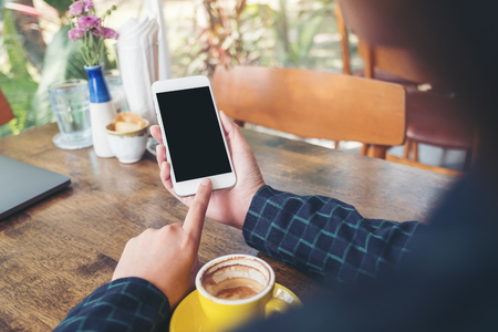 Mockup image of a hand holding and pointing at white mobile phone with blank black desktop screen with yellow coffee cup on wooden table in cafe Stock fotó
